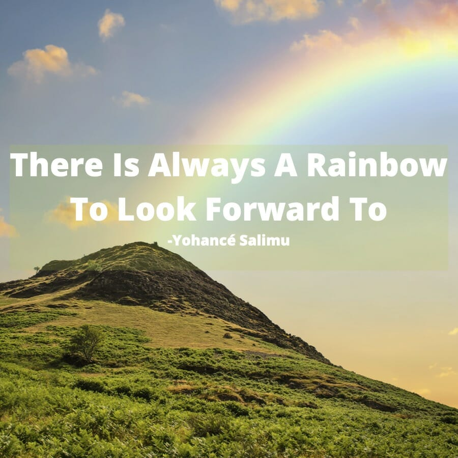 positive words over a hill with a rainbow